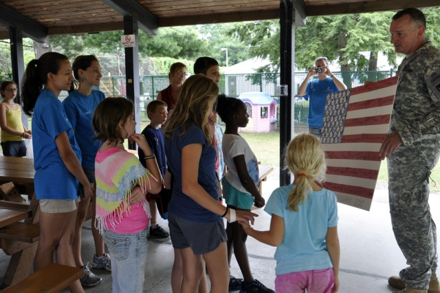 Col. Mark F. Migaleddi, right, accepting a U.S. National Flag that was created by the children who are part of the Arsenal's summer camp program.
