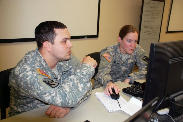 """Two officers of the 201st Military Intelligence Battalion prepare analysis based on information obtained from a """"detainee"""" during training at the Intelligence Security Command Detention Training Facility at Camp Bullis, Texas."""