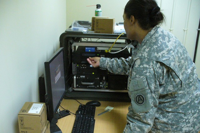 Sgt. 1st Class Nichole Cunningham, the Area Support Group - Kuwait Class VIII warehouse non-commissioned officer in charge, performs daily maintenance on the DMLSS server.