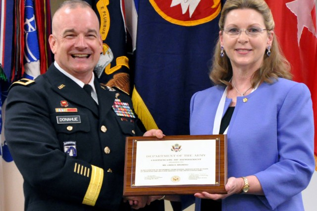 Brig. Gen. Scott F. Donahue, U.S. Army Reserve Command G3/5/7, poses for a photo with Ms. Linda Bruneau during a retirement ceremony, July 30, at Fort Bragg, N.C., honoring Bruneau for 40 years of civilian federal service.