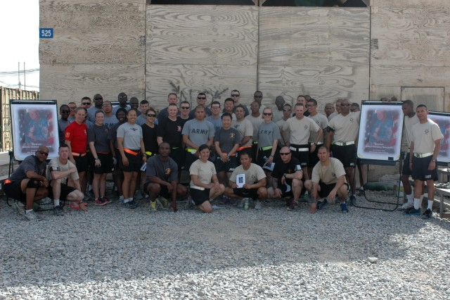 Soldiers and officers of the 45th Sust. Bde. gather for a group photo after the memorial CrossFit Workout of the Day for Staff Sgt. Robert Massarelli July 15 at the 45th Sust. Bde. CrossFit Gym, Kandahar Airfield, Afghanistan. The event consisted of three rounds of four exercises performed for the fastest time.