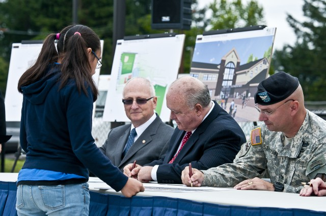 Undersecretary of the Army Joseph W. Westphal (center) and Col. Thomas Brittain (far right), Joint Base Lewis-McChord garrison commander, sign an Education of Military Children Covenant during a groundbreaking ceremony, July 30, 2012, signifying the official start of a year-long construction project to completely rebuild the JBLM's Hillside and Carter Lake Elementary Schools. The Department of Defense deemed the schools two of the top five in military communities across the U.S. in need of immediate attention during a nationwide assessment that justified a $250 million addition to the fiscal year 2011 department appropriations bill to fix the schools.