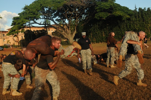 Soldiers of the 130th Engineer Brigade, 8th Theater Sustainment Command compete during the buddy carry portion of the amazing race during Engineer Week on Watts Field, Schofield Barracks, July 23.