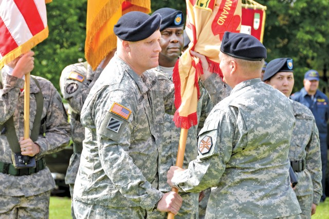 Lt. Col. Michael D. Sullivan, incoming commander of the U.S. Army Garrison Baumholder, receives the garrison colors from Col. Bryan D. DeCoster, USAG Baden-Wuerttemberg commander, July 20, during the change of command ceremony.