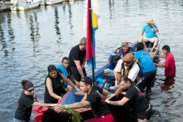 Soldiers with the 295th Quartermaster Company from Joint Base Lewis-McChord, Wash., pull a canoe onto a trailer that will pull the watercraft out of the water. The canoe landing was part of the Paddle to Squaxin 2012, an annual event where members of Native American tribes come together in a show of unity in part by paddling to the host tribe's area.