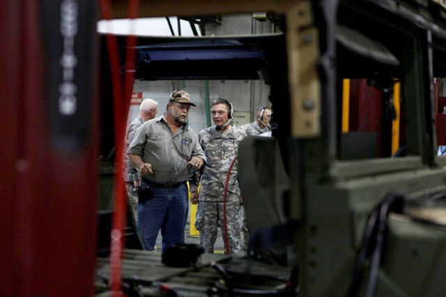 Maj. Gen. Michael J. Terry, Commanding General, U.S. Army TACOM Life Cycle Management Command talks with Russell Anderson, chief, High Mobility Multipurpose Wheeled Vehicle Tactical Division during a tour of Red River July 25.