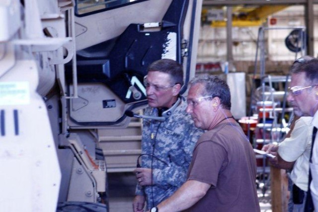 Maj. Gen. Michael J. Terry, commanding general, TACOM Life Cycle Management Command talks with an employee during a tour of the Mine Resistant Ambush Protected Vehicle production line at Red River Army Depot.