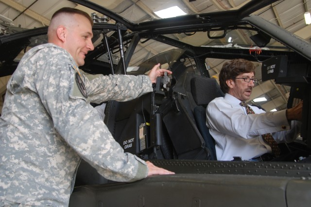 Sgt. 1st Class Ron Bolinsky, (left) committee chief in charge of Initial Entry Training students, 128th Aviation Brigade, Fort Eustis, Va., explains the process of what it takes to operate an AH-64D Apache Longbow helicopter at a Felker Army Airfield hangar to Trent Di Giulio of Dallas and member of the Defense Orientation Conference Association during DOCA's visit to Training and Doctrine Command the afternoon of July 30 at Fort Eustis, Va.