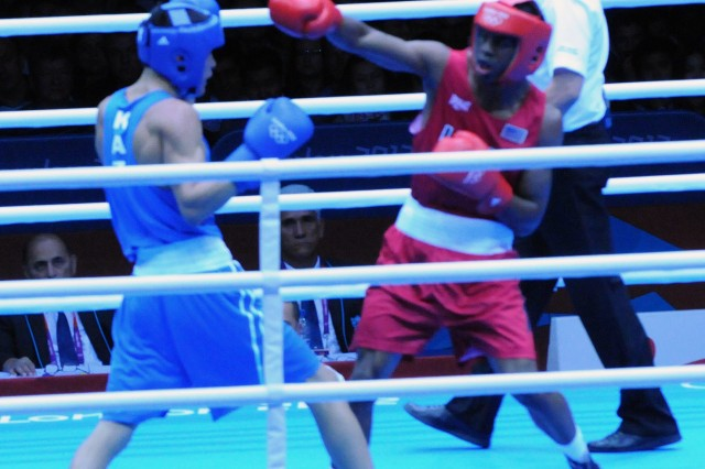 Marine Corps Sgt. Jamel Herring throws a punch at Kazakhstan's Daniyar Yeleussinov in an Olympic light welterweight bout, July 31, 2012, at the ExCel Centre in London.