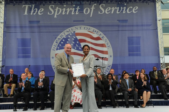 "Ms. Sharon Bliey receives the ""Spirit of Service"" Recognition Certificate from Mr. Thomas R. Lamont, Assistant Secretary of the Army for Manpower and Reserve Affairs"