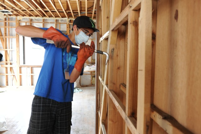 Robert Corneliussen, 15, a member of Camp Zama, Japan, disaster relief volunteer group, removes nails from the wall of the apartment which was damaged by the tsunami.