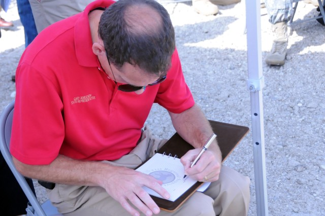 Florida State Representative Gary Aubuchon signs a guest book during a ground breaking ceremony for a new Army Reserve cemter in Cape Coral, Florida on July 28. The guest book will also be present for the building's ribbon cutting in approximately 14 months.