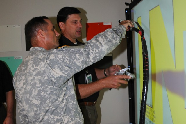 Col. Michael C. Aid, ACLC commander, is given a demonstration of the LaserPaint laser-guided spray training aid of the new STAR4D program by AFS training analyst Tom Elsbernd at Cairns Army Airfield July 26.