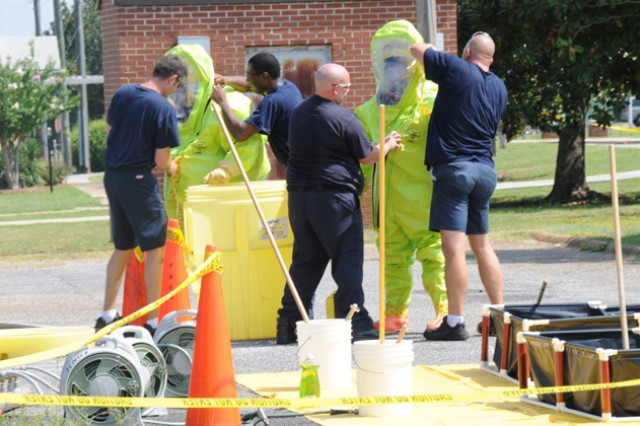HAZMAT team members help each other out of their suits as they return from a building where authorities received a call about a suspicious package July 26. No hazardous materials were found during the search.