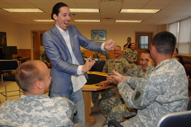Wayne Hoffman successfully bends a quarter inside the hand of Sgt. 1st Class Shawn Redondo, a senior small group leader at the NCOA, during a performance on July 27.
