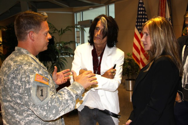 Col. Jimmie Jenkins, U.S. Army Space and Missile Defense Command/Army Forces Strategic Command chief of staff, explains the command's mission to Aerosmith lead guitarist, Joe Perry, and his wife, Billie, during a visit to the command on Peterson Air Force Base, Colo., Aug. 1.