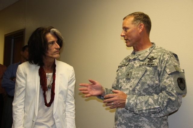 U.S. Army Space and Missile Defense Command/Army Forces Strategic Command Deputy Commanding General for Operations Brig. Gen. Timothy Coffin thanks Aerosmith lead guitarist Joe Perry for visiting the command on Peterson Air Force Base, Colo., Aug. 1.