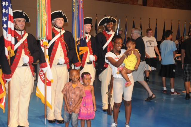 """Audience members mingle with performers inside Joint Base Myer-Henderson Hall's Conmy Hall, in Arlington, Va., after watching the Military District of Washington's time-honored tradition of the """"Twilight Tattoo."""""""