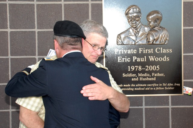 FORT CARSON, Colo. -- 1st Lt. Stephen A. O'Hearn hugs Charles Woods, father of Pfc. Eric P. Woods, at the unveiling of a plaque dedicating the Pfc. Eric P. Woods Soldier Family Care Center. O'Hearn was Eric Woods' platoon sergeant in Iraq.