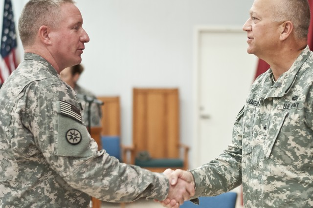 "Brig. Gen. Bud R. Jameson Jr., a resident of Sherwood, Ark., shakes hands with Col. David Whaling, a resident of Greenville, Pa., during a ceremony for the Soldiers of the 316th Sustainment Command (Expeditionary). The ceremony commemorates the earning of the unit's patch as their shoulder sleeve insignia former-wartime service at Camp Arifjan, Kuwait, Aug. 2. ""I want you to be able to wear this patch with pride, knowing the legacy that you build here is going to be unmatched in the ESC and sustainment community,"" said Jameson, the commanding general of the 316th."