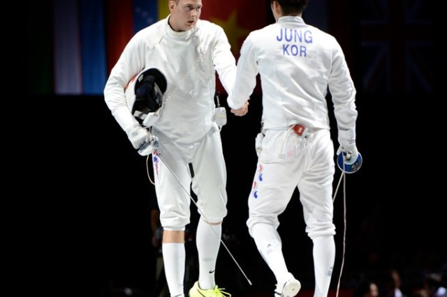 U.S. Air Force Capt. Seth Kelsey (left) congratulates Jinsun Jung afer the Korean fencer scores in sudden-death overtime to win the Olympic bronze medal in épeé at the ExCel Centre in London Aug. 1.
