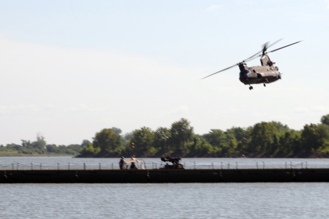 A Chinook helicopter does a fly-by over the completed Improved Ribbon Bridge spanning the Arkansas River, as part of River Assault 2012 at Fort Chaffee, Ark. The bridge, consisting of individual floats pieced together, was completed in three hours.
