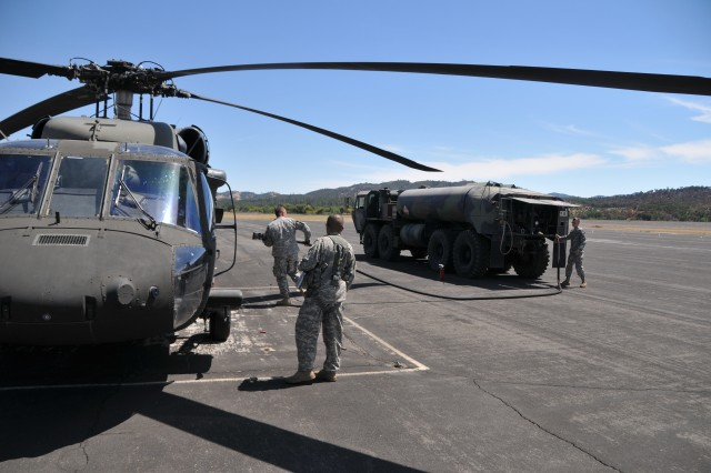 Aviation fuelers SPC Dennis Snay (left) and SPC Cody Miarer (far right) team up to top-off Blackhawk at Tusi Airfield. The petroleum supply specialists provide fuel for ground vehicles and aircraft at Fort Hunter Liggett.
