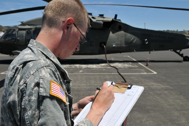Aviation fuel specialist SPC Cody Miarer checks information during helicopter refueling operations at Tusi Airfield at Fort Hunter Liggett. Tusi has nearly 3 dozen helipads and can accomodate rotory aircraft as well as the U. S. Marine V-22 Opsprey aircraft.