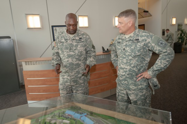 Sgt. 1st Class Reginald Snell, non-commissioned officer in charge of the Incident Response Training Department, briefs Sgt. Maj. of the Army Raymond F. Chandler III using a facility model of the 1st Lt. Joseph Terry Chemical, Biological, Radiological and Nuclear Responder Training Facility at Fort Leonard Wood Aug. 2.