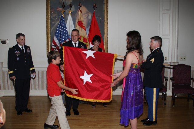 """Assisted by his son, Michael and daughter, Giovanna, Maj. Gen. John """"Sonny"""" Uberti"""" unfurls his two-star general flag while Lt. Gen. Mike Ferriter, commanding general of Installation Management Command and Assistant Chief of Staff for Installation Management and Uberti's wife, Linda look on. Sgt. John Denney, U.S. Army Garrison Fort Hamilton holds the flag."""