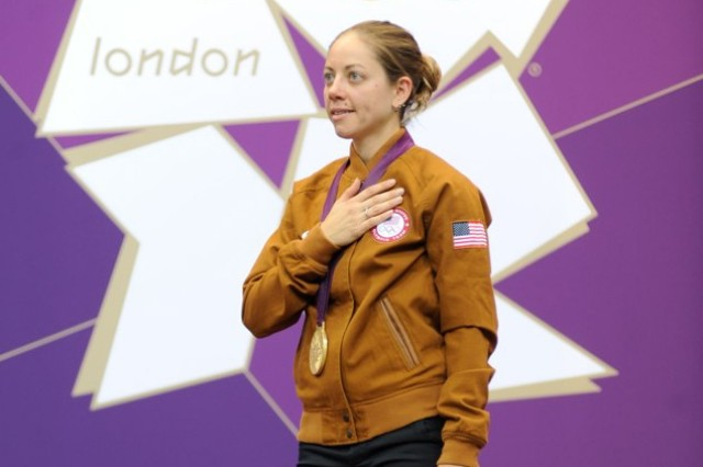 Jamie Gray, wife of U.S. Army Marksmanship Unit shooter Staff Sgt. Hank Gray, stands on the podium with her hand over her heart during the U.S. national anthem after she was awarded gold for the women's 50-meter three-positions rifle event Aug. 4, 2012, at the Royal Artillery Barracks in London.