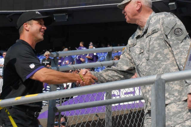 Baltimore Ravens Head Coach John Harbaugh welcomes Maj. Gen. James A. Adkins, Maryland National Guard adjutant general, to the team's fifth annual Military Appreciation Day before open practice at M&T Bank Stadium in Baltimore, Md., held Aug. 4, 2012. The Ravens reserved approximately 3,500 seats for service members, veterans and military families.