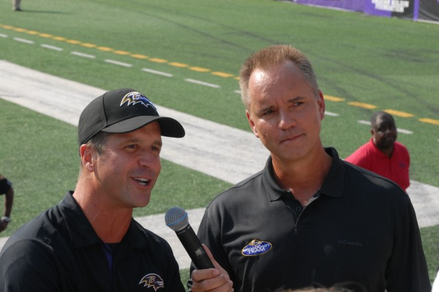Baltimore Ravens Head Coach John Harbaugh thanks service members at the team's fifth annual Military Appreciation Day during an interview with Ravens announcer Gerry Sandusky before open practice at M&T Bank Stadium in Baltimore, Md., held Aug. 4, 2012. The Ravens reserved approximately 3,500 seats for service members, veterans and military families.