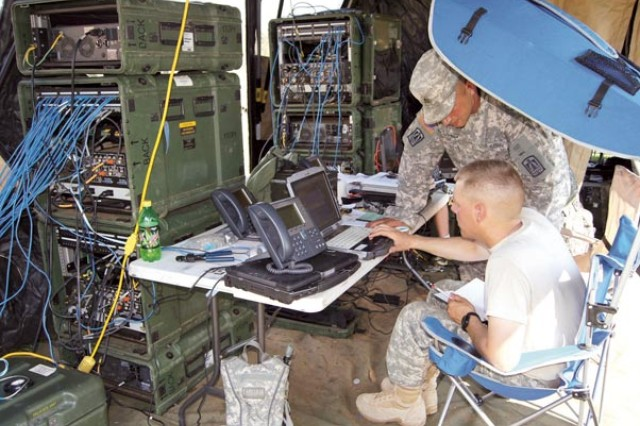 Sgt. Nunzio Incorvaia and Spc. Robert Surran, Company B, 40th Expeditionary Signal Battalion, provide internet capabilities for 514th Medical Company's main tactical operations center.