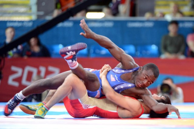 Russia's Mingiyan Semenov turns U.S. Army World Class Athlete Program Sgt. Spenser Mango (top) en route to a 2-0, 1-0 victory in the first round of repechage in the 55-kilogram/121-pound Greco-Roman division of the Olympic wrestling tournament, Aug. 5, 2012, at ExCel North Arena in London. Mango went 1-2 and finished ninth in his weight class.