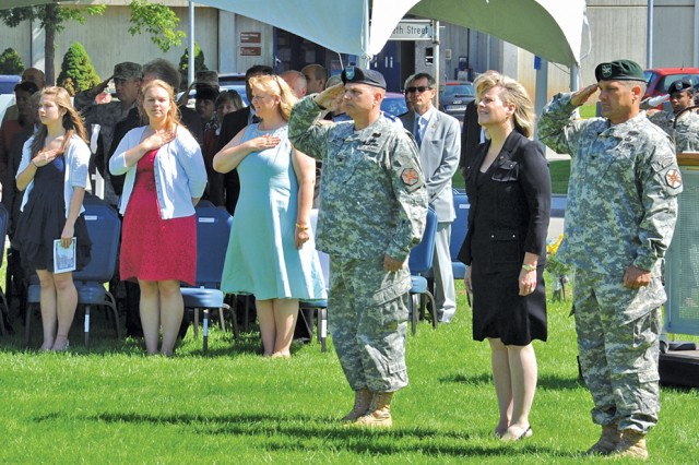 Col. John P. Stack (from right), the incoming USAG Stuttgart commander; Kathleen Marin, the IMCOM Europe regional director; and Col. Carl D. Bird, the outgoing commander, render honors as the U.S. and German anthems are played during the change of command ceremony July 23.