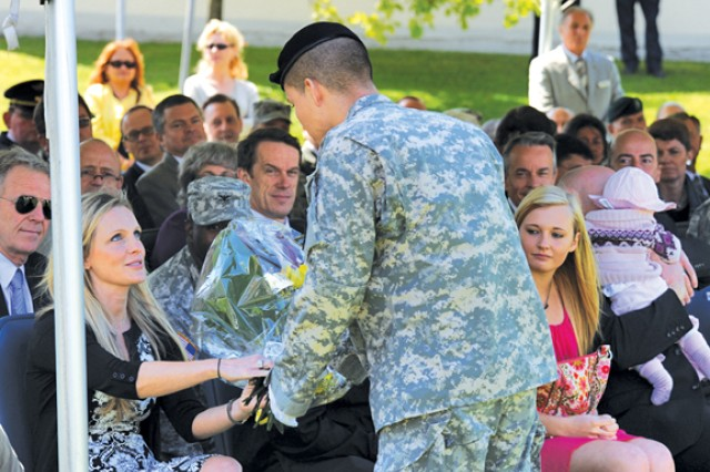 Staff Sgt. Victor M. Ortiz, USAG Stuttgart's 2012 NCO of the Year, presents Petrina Stack, wife of incoming garrison commander Col. John P. Stack, with a bouquet of yellow roses.
