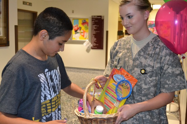 """Daniel Gonzalez the last patient of the afternoon received a """"thank you for waiting patiently"""" gift basket at Keller Army Community Hospital's mass school physical day, Thursday, Aug 2."""