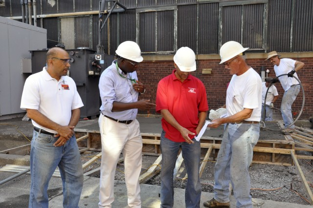 Arsenal Electrical Engineer Benjamin Dedjoe, second from left, discussing with the Pichardo Development Corp. contractors the test results of the concrete that was being poured at an electrical substation.