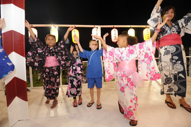 Community members perform the moves of a traditional Japanese Bon dance on a tower at Rambler Field on Camp Zama, Japan, during the post's 53rd annual Bon Odori Festival, Aug. 4, 2012. More than 30,000 people attended the event.