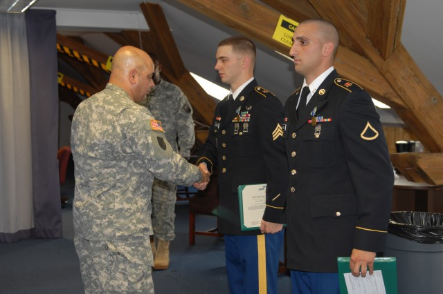 Command Sgt. Maj. Ismael Rodriguez, the 16th Sustainment Brigade command sergeant major, presents Sgt. Alva Barnhart of the 106th FM Co. and a native of Lincoln, Neb., and Pfc. Joseph McNulty with the 12th Chemical Company and a native of Seaside Heights N.J., with the Army Achievement Medal at the 16th Sust. Bde. headquarters in Bamberg, Germany July 25. McNulty and Barnhart won the titles of Warrior and Warrior Leader of the Quarter during the 16th Sust. Bde. Competition.