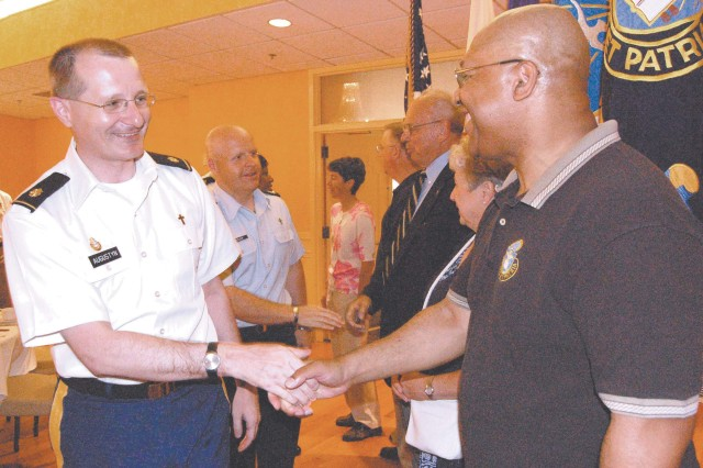 Installation catholic priest from Fort Meade, Md., Maj. Boguslaw Augustyn (left) shakes hands with the Regimental Sgt. Maj. of the Chaplain Corps Stephen Stott (right) during the fellowship luncheon for the anniversary of the U.S. Army Chaplain Corps July 27.