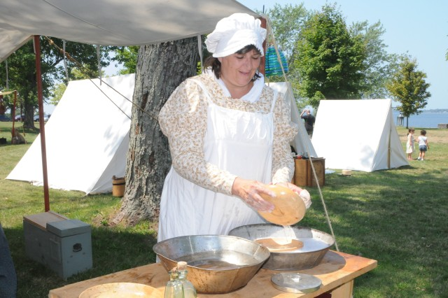 Teal Abel, of Carthage, washes dishes at her campsite Saturday. Abel and her family participated in the annual War of 1812 bicentennial weekend in Sackets Harbor.