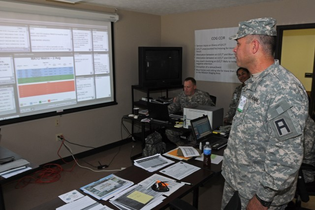 Col. John Dunleavy, commander, 205th Infantry Brigade, First Army Division East, reviews the status of training missions being supervised by First Army observer controllers, Aug. 2, 2012, at the First Army observer control operation center at North Vernon, Ind. Dunleavy serves as the senior training mentor for a group of First Army observer controllers at exercise Vibrant Response 13.