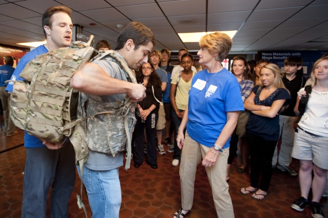 Tyler Brown and Jane Simpson of NSRDEC assist Yair Mega, Northeastern University Young Scholars Program mentor, as he tries on Army gear. NU Young Scholars watch before they try on the gear and attempt to cross a balance beam with all that extra equipment.