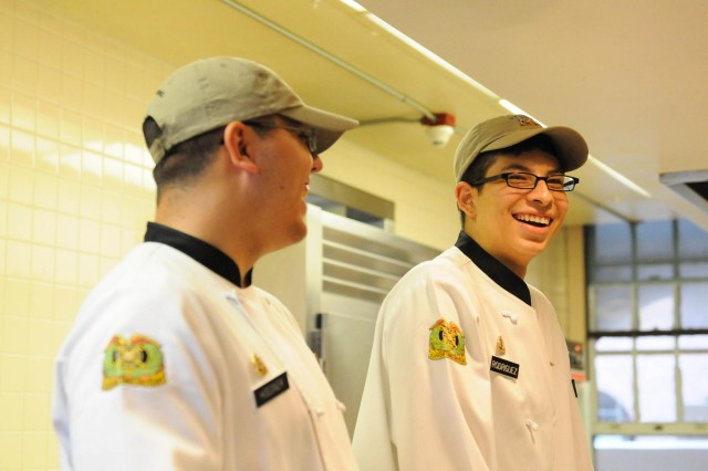 Spc. Cody Hogener (left) and Pvt. Jose Rodriguez share a laugh while serving dinner at I Corps Special Troops Battalion Dining Facility, Aug. 2, at Joint Base Lewis-McChord, Wash. Rodriguez has been skateboarding for more than six years and continues to enjoy his passion for skating at the parks provided by JBLM.