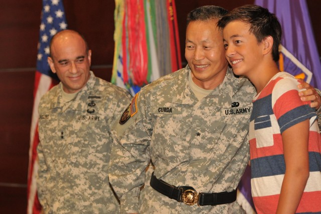 Brig. Gen. Stephen K. Curda with son, Major pose after Major assisted his father in donning his general