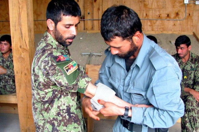 """An Afghan Uniformed Police officer practices bandaging a soldier from the Afghan National Army during a practical training exercise of a """"train the trainer"""" Combat Life Saver class in Paktika Province, Afghanistan. The course was led by the medics of Headquarters and Headquarters Company, 4th Brigade Special Troops Battalion, 4th Infantry Brigade Combat Team, 1st Infantry Division."""