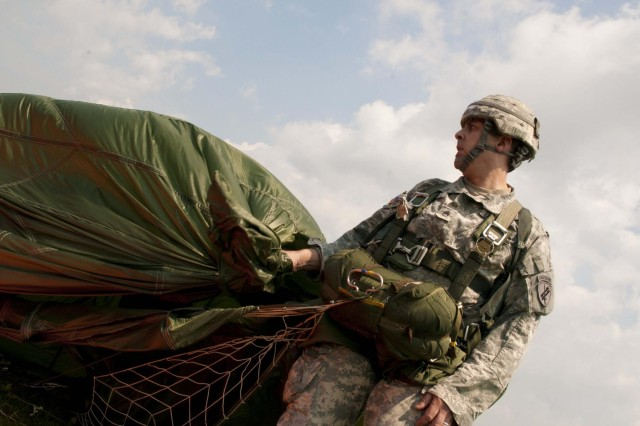 Staff Sgt. Stanley Meyer, 352nd Civil Affairs Command, gathers his parachute after hitting the target at Leapfest on August 4, 2012. The two-day competition brought 64 teams from all across the world to Castle Drop Zone in West Kingston, R.I.