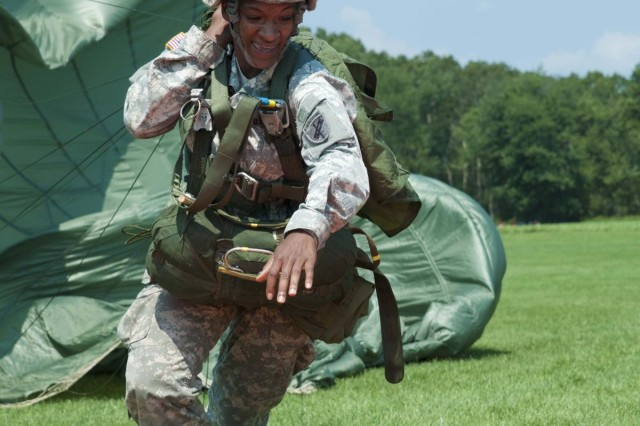 Spc. Ciera Terry, U.S. Civil Affairs & Psychological Operations Command (Airborne), pulls her parachute while attempting to touch the target in Leapfest 2012 on Castle Drop Zone, West Kingston, R.I. The 10 mph wind made it difficult for those who landed past the target forcing Terry and others to pull their parachute upwind to reach their mark.